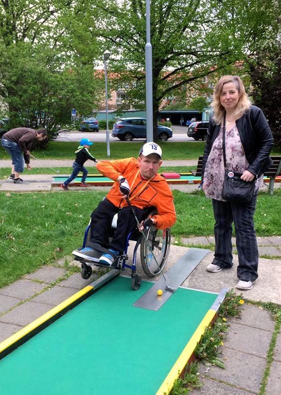 En man sitter i rullstol och spelar minigolf, en kvinna står bredvid.