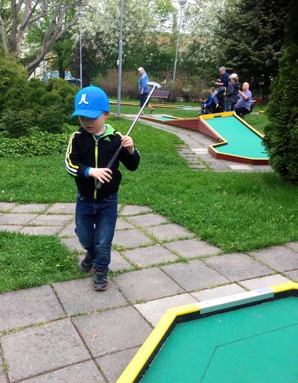 En liten pojke med en golfklubba