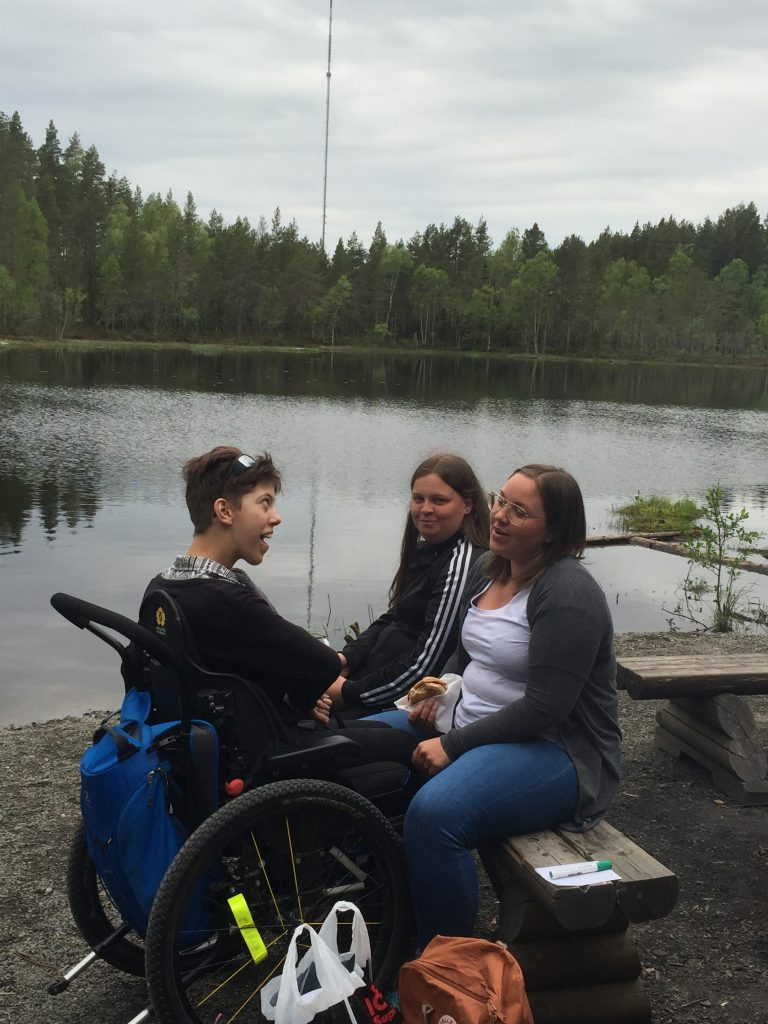 Tre tjejer sitter vid en sjö och pratar